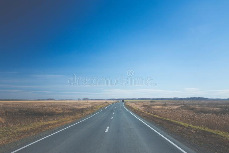 Empty road through the autumn fields stock photography