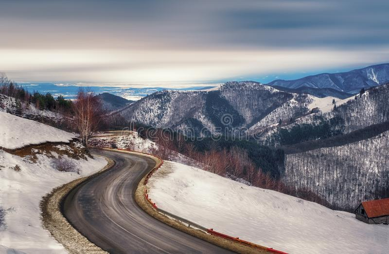 The empty road coming through the winter mountains royalty free stock photo