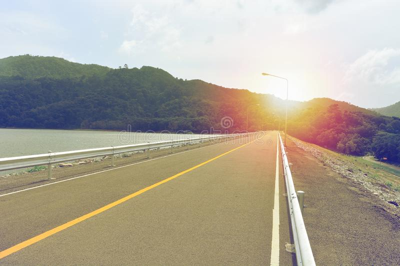 Asphalt road with yellow lane dividing line in the middle on dam stock photography