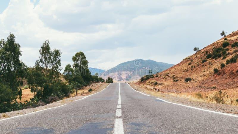 Empty road through desert stock photos