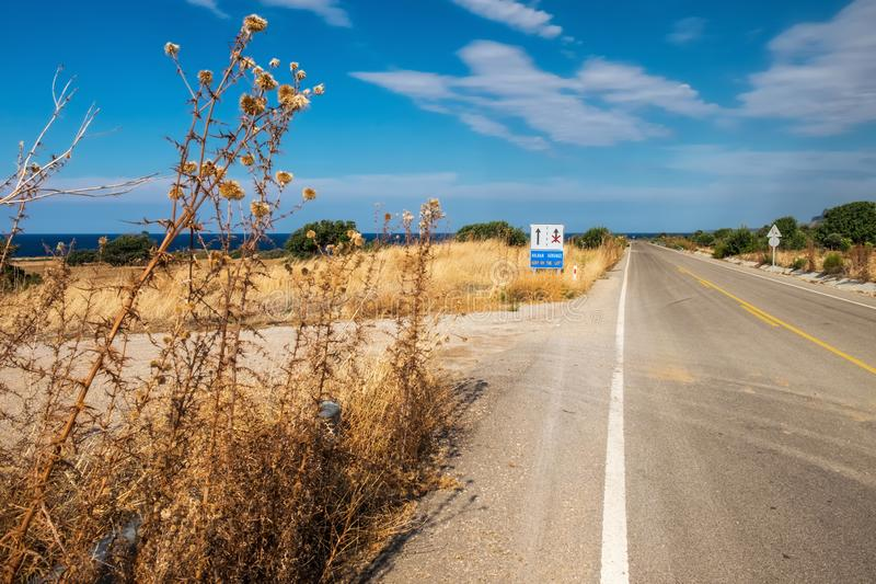 The empty road goes through the desert Cyprus coastline with dry prickly grass under the blue sky. royalty free stock image