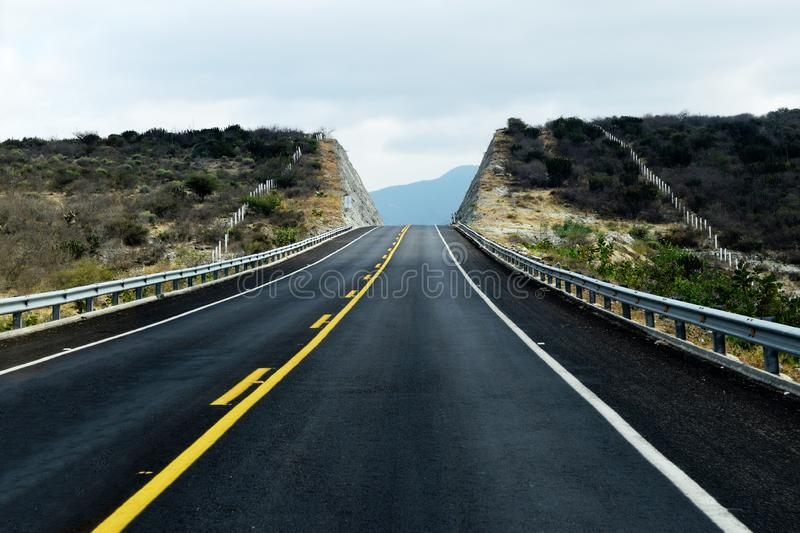 Empty road leading to the mountains. Big empty black road going uphill towards the mountains. Photo taken outside Oaxaca, Mexico royalty free stock images