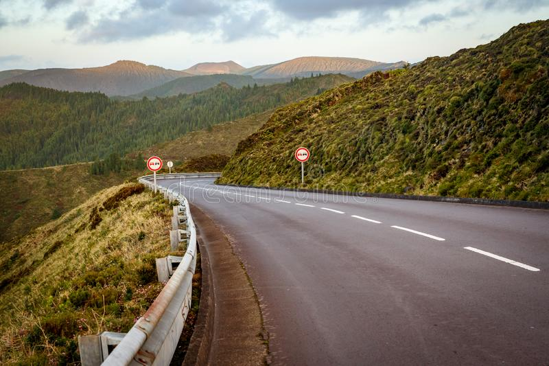 Empty road in the mountains. No overtaking sign. Empty road in the mountains. Sunset. No overtaking sign stock photo