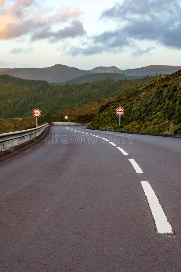 Empty road in the mountains. No overtaking sign. Empty road in the mountains. Sunset. No overtaking sign stock images