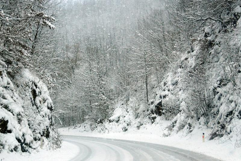 Empty road in the mountains during a snowfall. royalty free stock photos