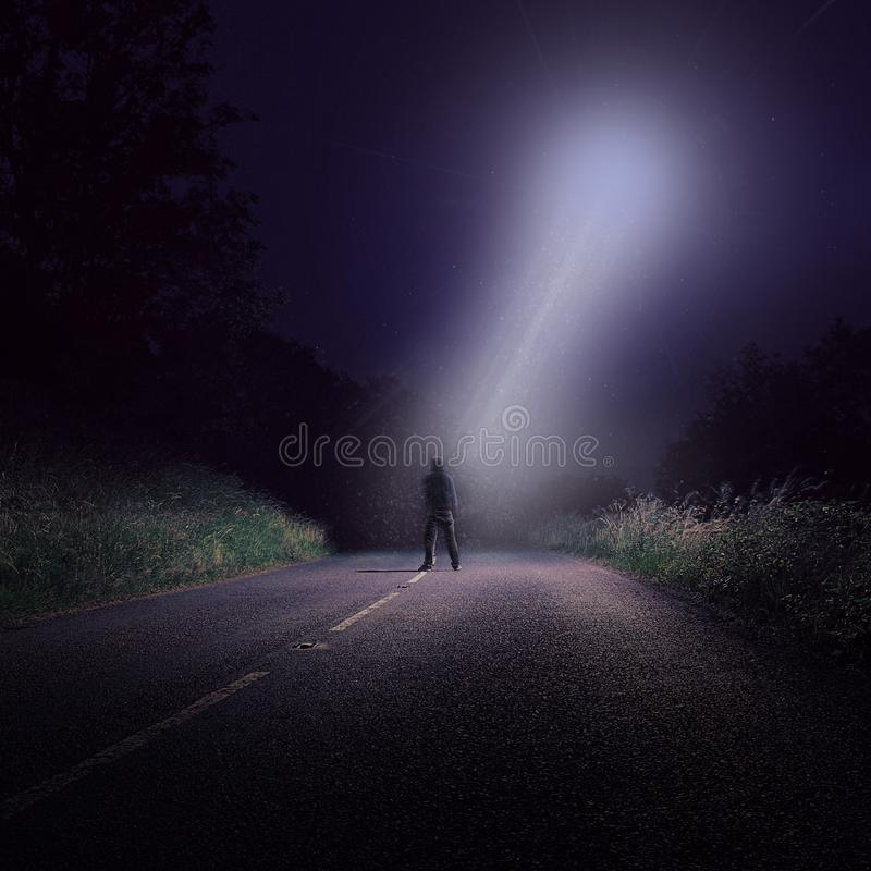 An empty road at night with a lone figure looking up at bright UFO with a white beam of light coming down stock photography