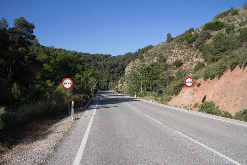 Empty road with no overtaking signs. Empty road through the Parque Naturel sierra Magina, Jaen province, Spain with no overtaking signs stock photography