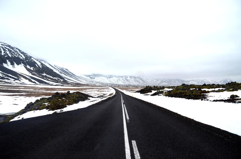 Empty road through snow and mountains royalty free stock images