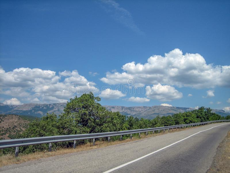 Empty road in the southern hilly-mountainous area on a hot summer day royalty free stock photo