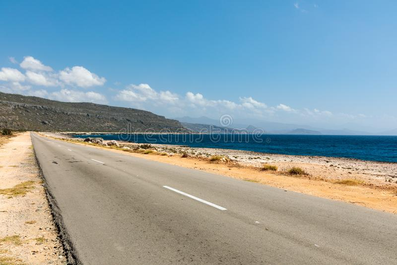 Empty road to guantanamo with the ocean Cuba royalty free stock photos