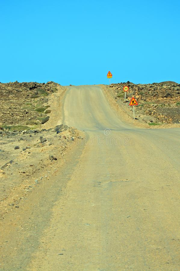 Empty road with warning signs. Empty, steep, yellow road with a row of warning signs on the right side on the north of Fuerteventura, nearby Corralejo stock photos