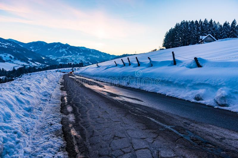 Sky reflection on empty, destroyed cracked asphalt road in winter. Big snow around and snow-covered mountains at sunset. Austria royalty free stock photos