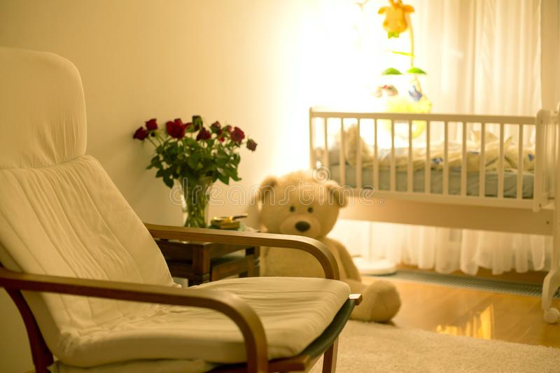 Empty rocking chair in a baby boy room with big teddy bear, crib royalty free stock image