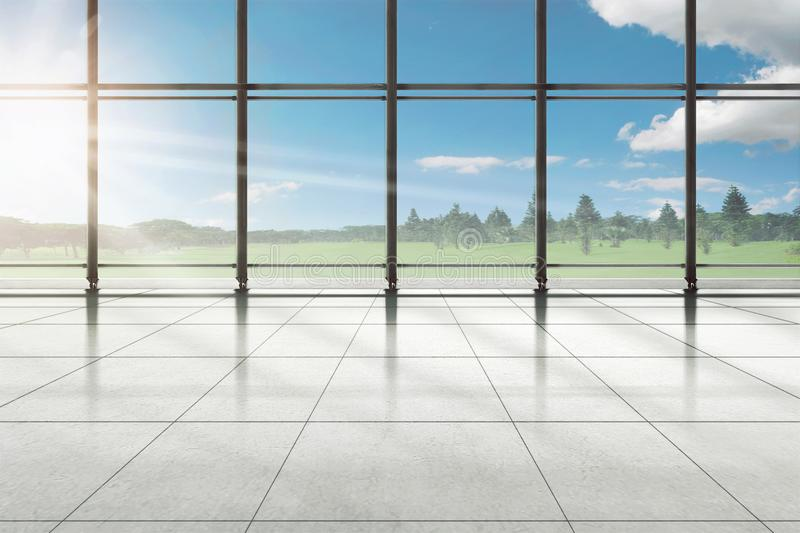 Empty room of airport terminal with trees and green field. Seen through the window stock image