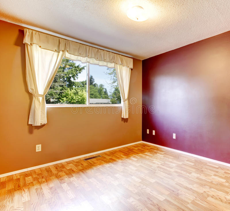 Empty room with contrast walls. Empty room with burgundy and brown walls, hardwood floor. View of window with soft ivory curtains royalty free stock photo