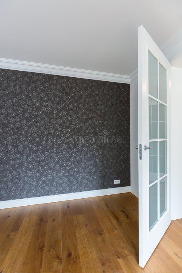 Empty room with grey wallpaper. Spacious empty room with grey wallpaper in modern house stock photo