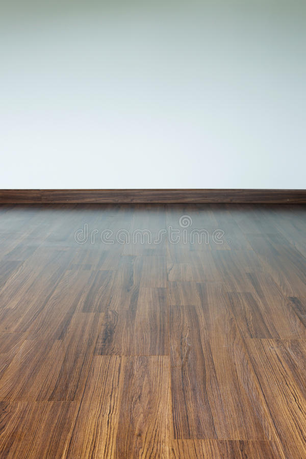Empty room interior, brown wood laminate floor. And white mortar wall royalty free stock photography