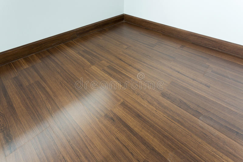 Empty room interior, brown wood laminate floor. And white mortar wall royalty free stock photo
