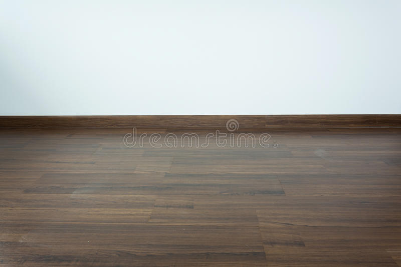 Empty room interior, brown wood laminate floor. And white mortar wall background royalty free stock image
