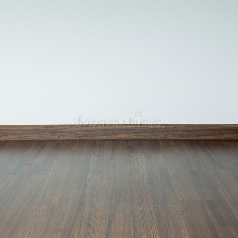 Empty room interior, brown wood laminate floor. And white mortar wall background royalty free stock photos