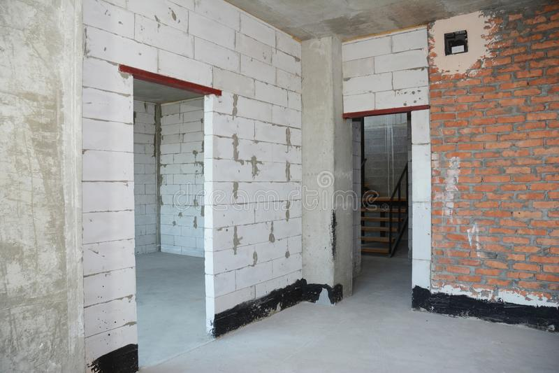 Empty room interior build with white and red bricks, plastering wall, waterproofing floor, metal door lintel royalty free stock photo