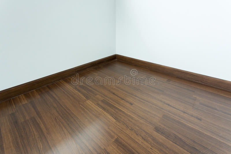 Empty room interior, white mortar wall background. Empty room interior, brown wood laminate floor and white mortar wall royalty free stock photos