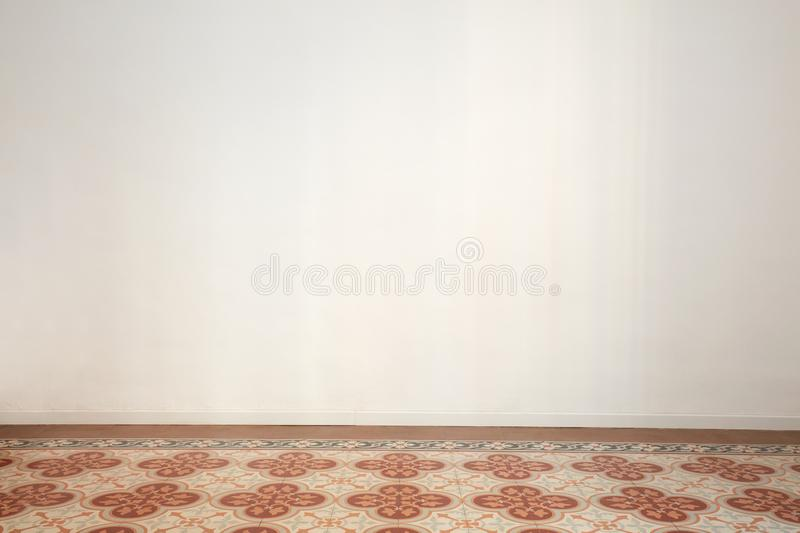 Empty room with white wall and ancient tiled floor in a renovated apartment royalty free stock photography