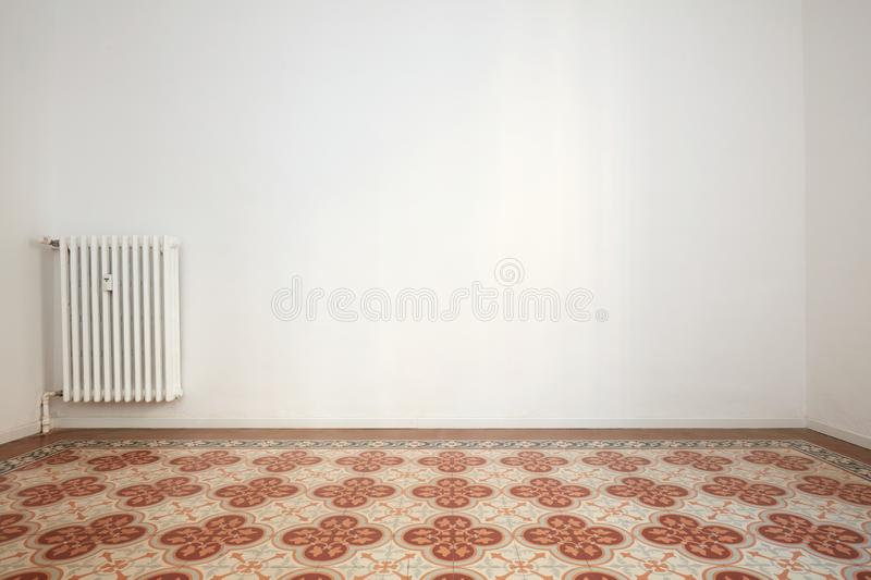 Empty room with white wall and tiled floor with floral decoration royalty free stock image