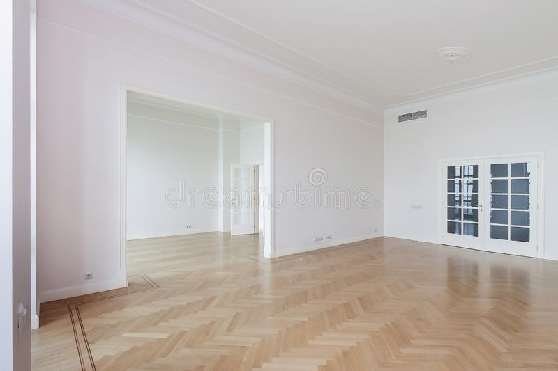 Empty room with whitewashed floating laminate flooring and newly painted white wall in background stock image