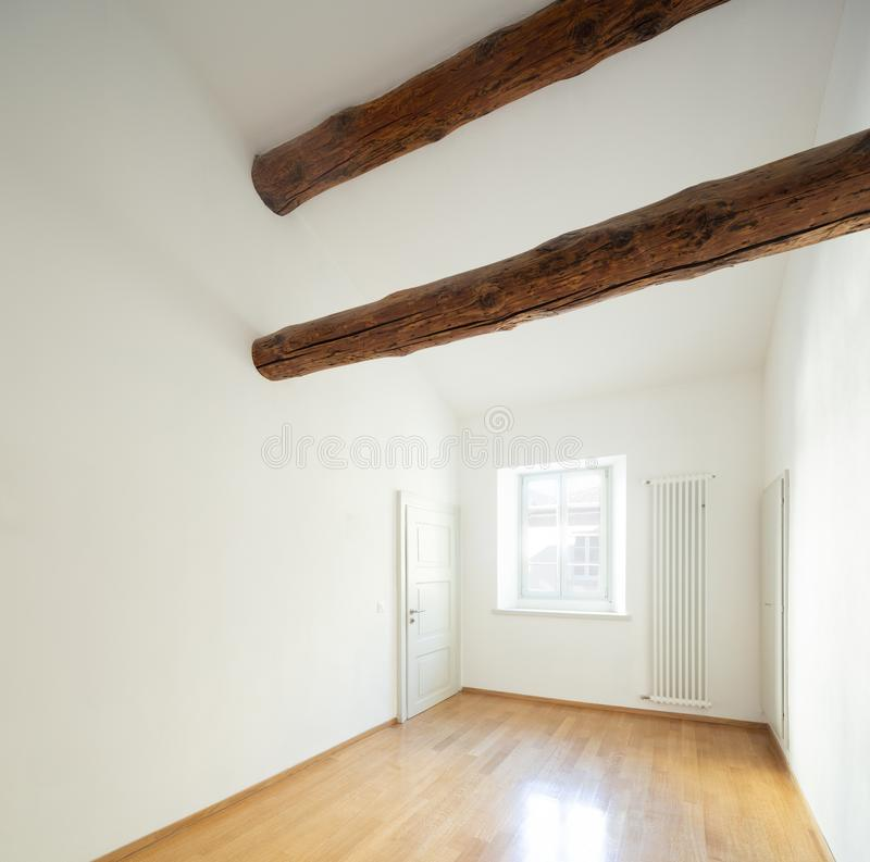 Empty room with wooden beams and parquet in refurbished apartment royalty free stock photos