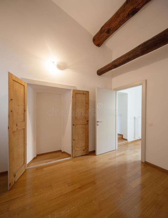 Empty room with wooden beams and parquet in refurbished apartment stock images