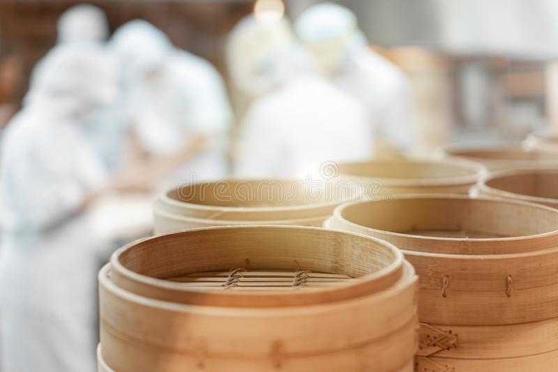 Empty round dim sum trays with chefs preparing the handmade dumplings in the background stock images