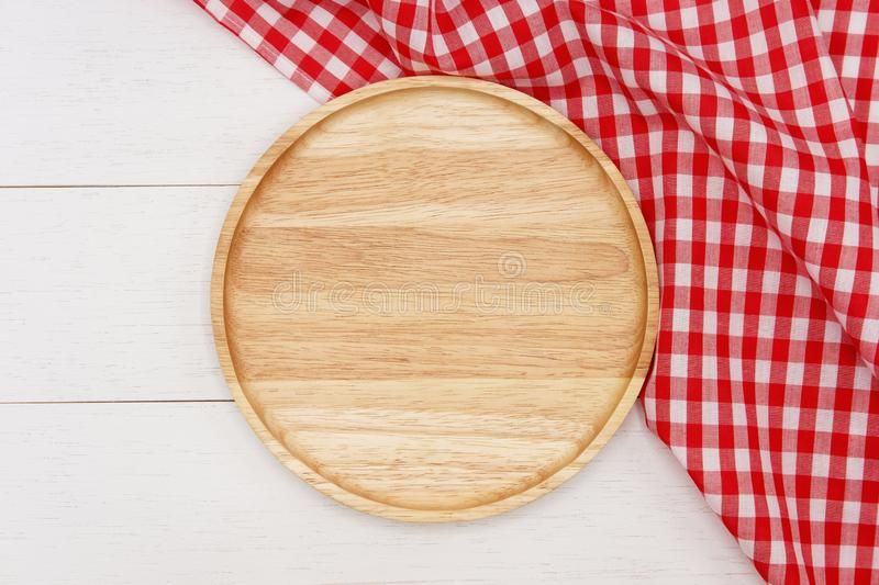 Empty round wooden plate with red gingham tablecloth on white wooden table. Top view image royalty free stock photography