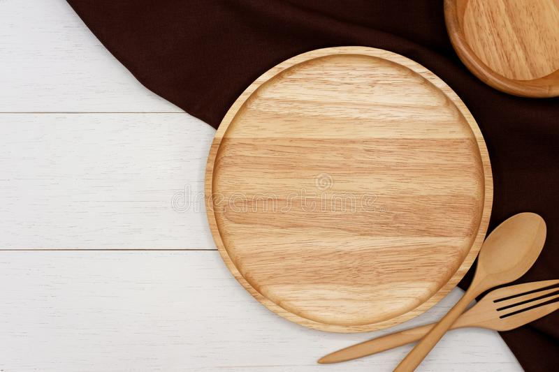 Empty round wooden plate with spoon, fork and dark brown tablecloth on white wooden table. royalty free stock photos