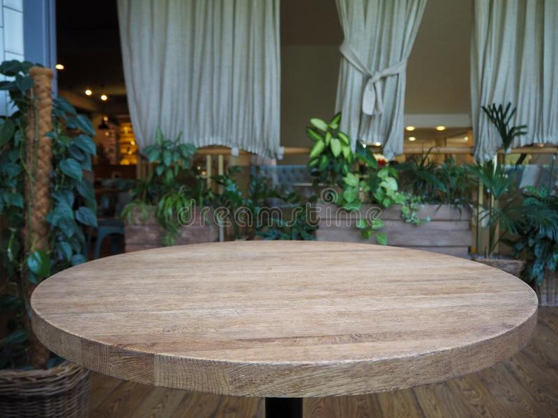 Empty round wooden table in a restaurant on the background of green plants stock photos