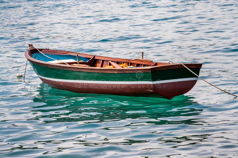 Empty rowing boat floating in the water. Empty green, white, and brown rowing boat, surrounded by water in the Bosporus, Istanbul, Turkey stock image