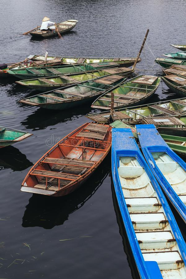 Empty rowing boats stop over the river with a man wearing white shirt and conical hat rowing boat in background. royalty free stock image