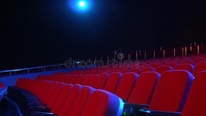 Empty rows of seats in cinema hall. Empty movie theater with red seats in darkened room with projector light on royalty free stock photo