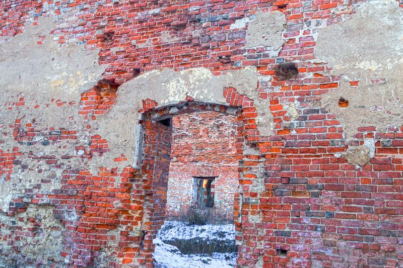 Empty ruined brick house empty door opening weathered old wall view of the courtyard covered with snow stock photos