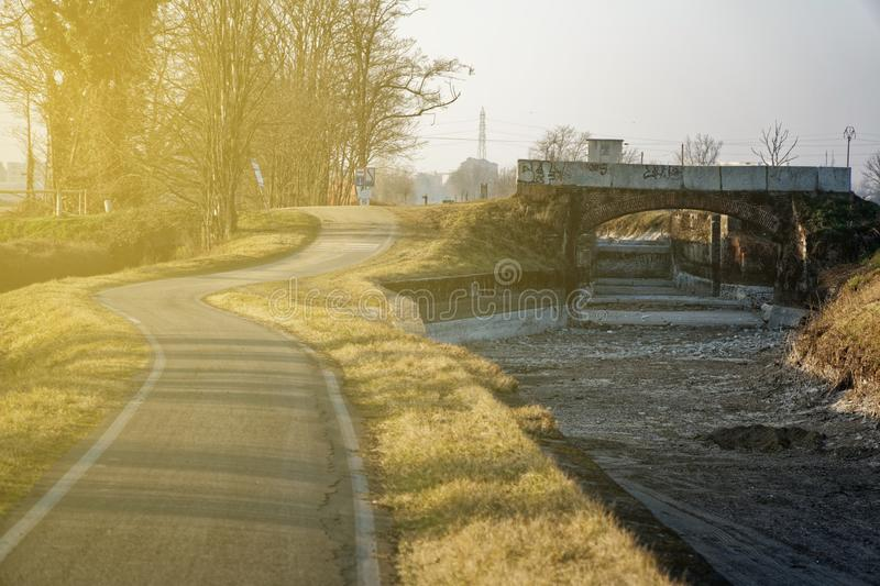 Empty running road near dry water canal. royalty free stock image