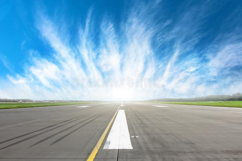Empty runway strip with markings with beautiful clouds on the horizon. Empty runway strip with markings with beautiful clouds on the horizon royalty free stock images