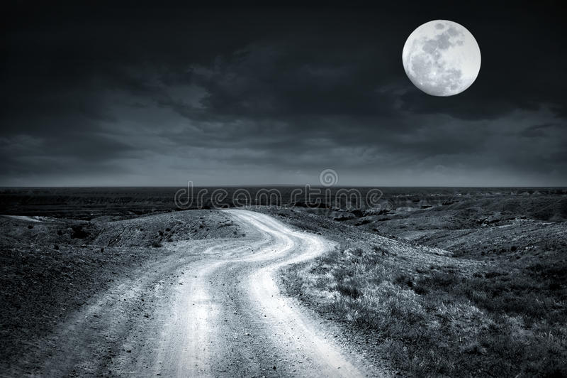 Empty rural road going through prairie at full moon night royalty free stock photo