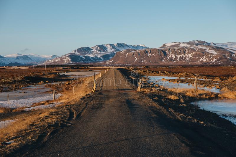 Empty rural road and snow-covered mountains. In iceland royalty free stock photography