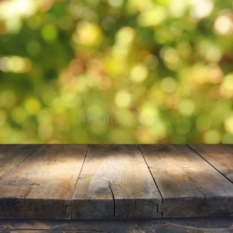 Empty rustic table in front of green spring abstract bokeh background. product display and picnic concept. Empty rustic table in front of green spring abstract royalty free stock photos