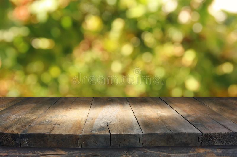 Empty rustic table in front of green spring abstract bokeh background. product display and picnic concept. royalty free stock photos