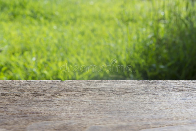 Empty rustic table in front of spring beautiful field background. product display and picnic concept. Horizontal wooden floor on top of blurred background of royalty free stock photo