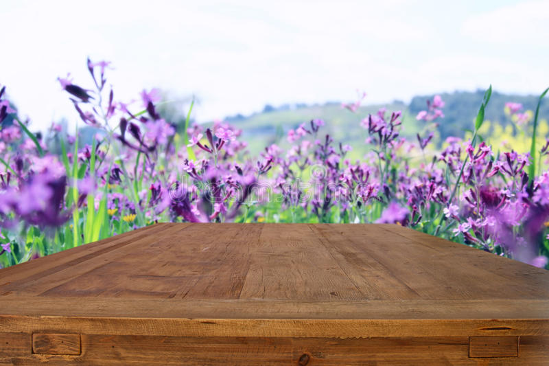 Empty rustic table in front of spring beautiful field flowers. Background. product display and picnic concept royalty free stock photos