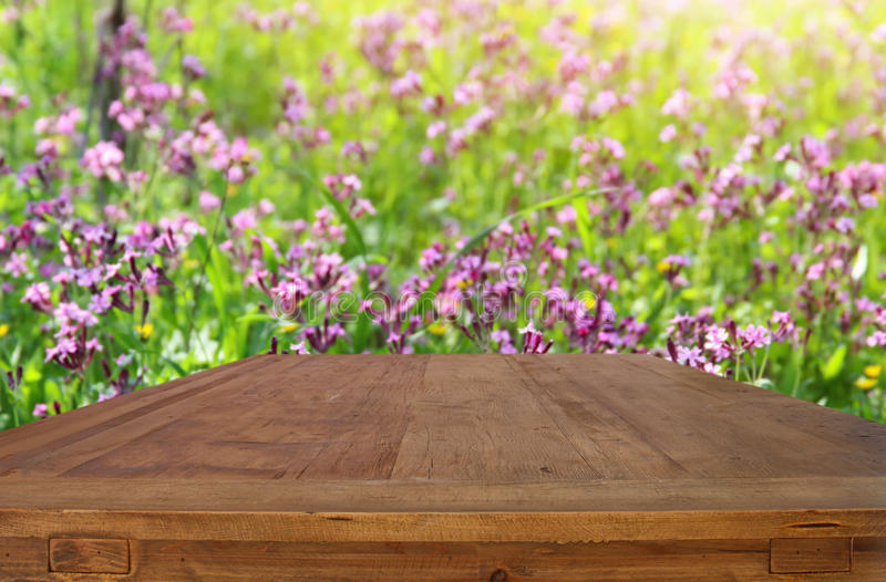 Empty rustic table in front of spring beautiful flowers background stock photos