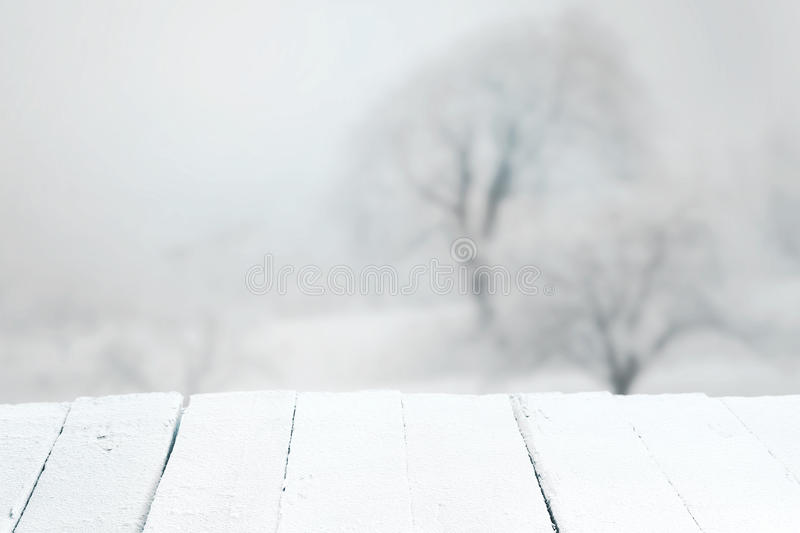 Empty rustic table in a winter landscape. Empty rustic white snow covered wooden table in the foreground of a misty a winter landscape suitable for product stock photos