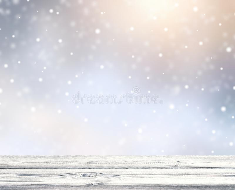 Empty rustic white wooden table. Snow falling and gold in rays of sun. Festive winter background. royalty free stock image